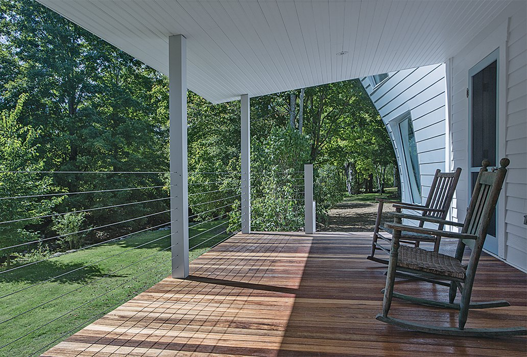 "The client requested a porch, so Givone built one with columns made of anodized aluminum, the same material used in the siding of the addition, and stainless steel cables. ""Even though it's a traditional, covered porch, it has very modern materials,"" he says.  Photo 10 of 22 in A Mind-Bending Renovation Brings a Bold, Modern Addition to an Old Farmhouse"