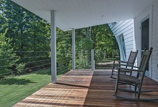 """The client requested a porch, so Givone built one with columns made of anodized aluminum, the same material used in the siding of the addition, and stainless steel cables. """"Even though it's a traditional, covered porch, it has very modern materials,"""" he says."""