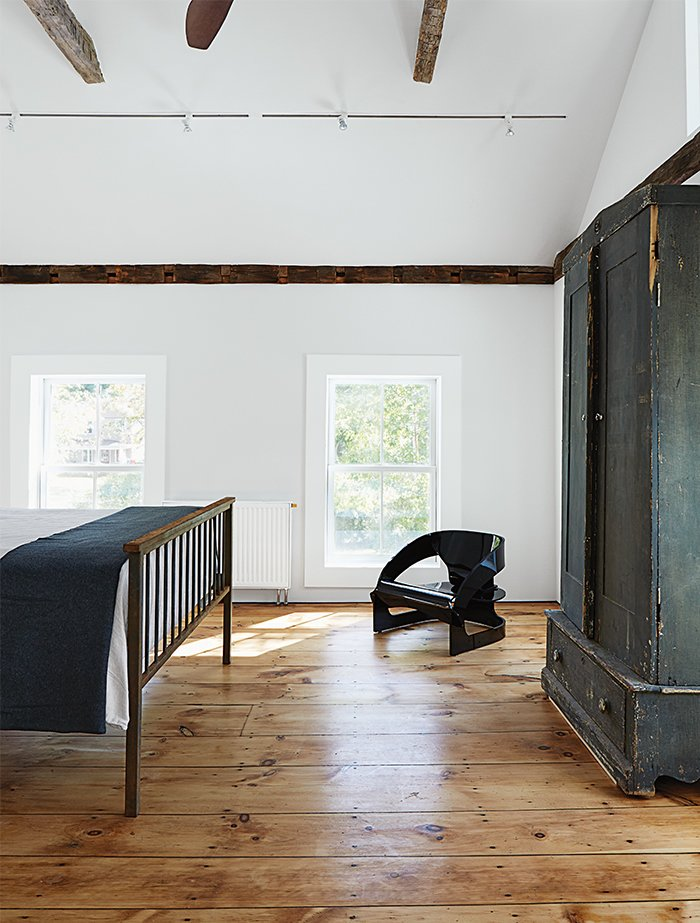 Kartell's 4801 chair occupies a corner of the master bedroom.  Photo 12 of 22 in A Mind-Bending Renovation Brings a Bold, Modern Addition to an Old Farmhouse