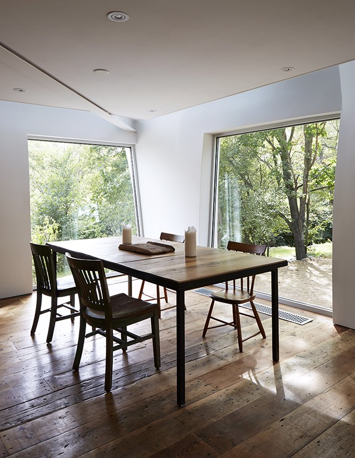 The new dining area is surrounded by swathes of glass. The windows were pivoted and installed at unusual angles in order to accommodate the undulating walls of the addition.  Photo 17 of 22 in A Mind-Bending Renovation Brings a Bold, Modern Addition to an Old Farmhouse