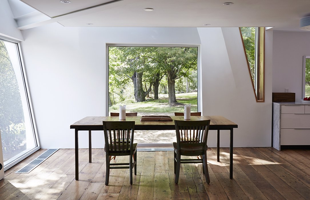The kitchen, dining room, and living room are connected in an open-plan arrangement.  Photo 18 of 22 in A Mind-Bending Renovation Brings a Bold, Modern Addition to an Old Farmhouse