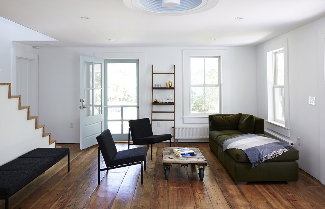 A bright, modern living area opens onto the porch.  Photo 19 of 22 in A Mind-Bending Renovation Brings a Bold, Modern Addition to an Old Farmhouse