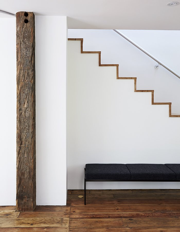 The modern staircase was built with the same salvaged wall planks that are used as flooring throughout.  Farmhouse from A Mind-Bending Renovation Brings a Bold, Modern Addition to an Old Farmhouse