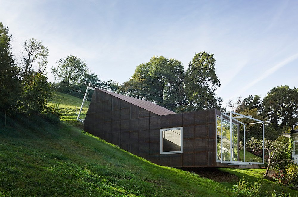 """Architect Christian Tonko played with a double metaphor when designing the Camera Lucida studio. The name of the cantileverd hillside space, Latin for """"bright chamber,"""" references the open window facing the valley below, as well as the skylight that bathes the workspace in natural light. Tagged: Exterior, House, and Metal Siding Material.  Photo 1 of 7 in Camera-Inspired Artist's Studio Offers Stunning, Wide-Angle Views"""