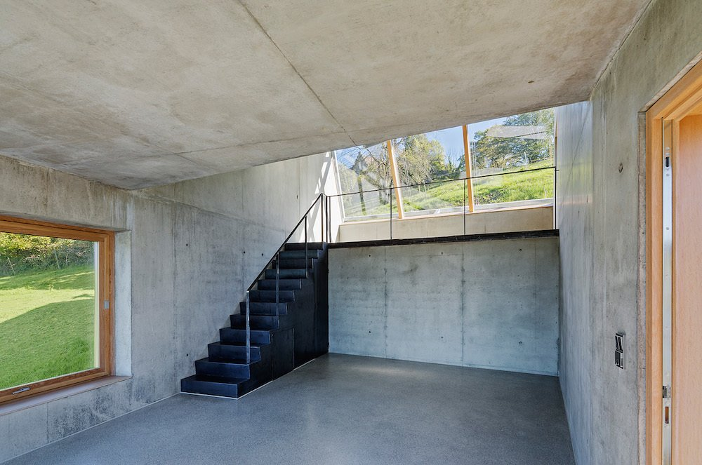 Staircase and Concrete Tread The single skylight helps light the artists' workstation. The simple interior, really a shed with smooth concrete surfaces, provides a stark yet airy space for creative pursuits.  Photo 5 of 7 in Camera-Inspired Artist's Studio Offers Stunning, Wide-Angle Views
