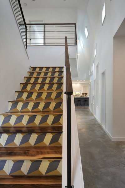An intricately detailed staircase leads to the central wing's second level. Its walnut treads and top rail harmonize with the welded steel rod railings. The geometric pattern on the staircase's risers comes from encaustic tiles that were handmade in Tuscaloosa, Alabama.