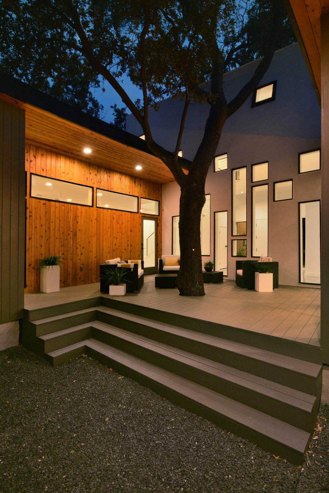 The central oak tree sprouts out of the rear deck. The atrium's array of windows draw the eye in the tree's direction. The wood cladding of the single-story wings provide a pleasant contrast with the central volume's stucco finish.  190+ Best Modern Staircase Ideas from A Mighty Oak Tree Frames This Family Home in Austin