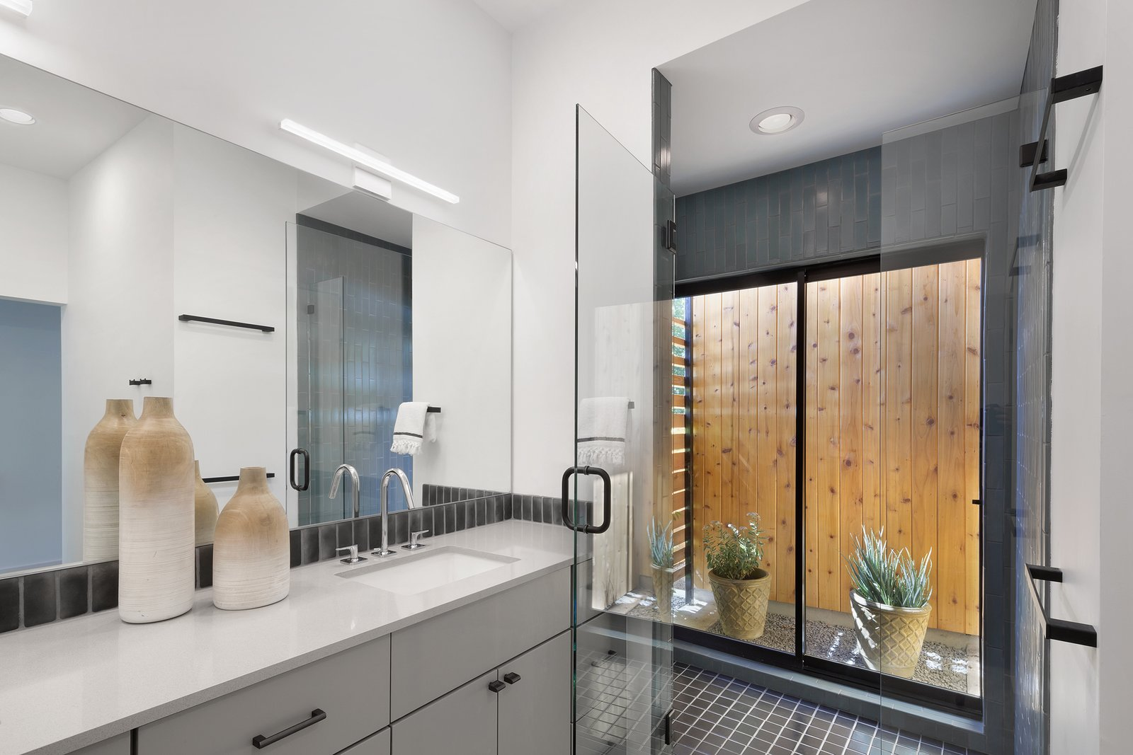 Thanks to a sliding glass door in the shower, even the master bathroom manages to retain a connection with nature. Custom cabinetry, a Sielstone Niebla counter and Kohler Verticyl sink, however, all offer compelling reasons to stay inside.  Photo 8 of 10 in A Mighty Oak Tree Frames This Family Home in Austin