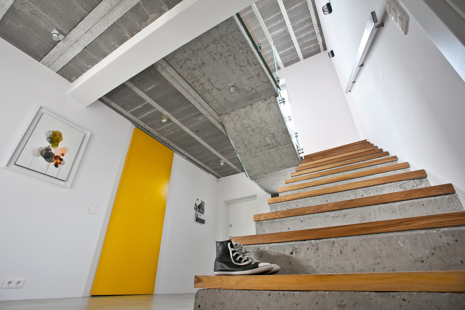 "Ceilings are typically composed of concrete beams and blocks that are covered with drywall and paint. But for this project, the architects left them bare to texturize the room. ""It creates a beautiful contrast with the snow white walls and splashes of yellow,"" they explain. The painting on the wall is by Magdalena Karpińska.  190+ Best Modern Staircase Ideas from A Modern Home Experiments with Exposed Concrete and Sliding Yellow Doors"