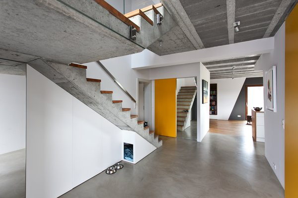 """A minimalist approach to design can make spaces feel thoughtful, bright, and more spacious than they really are—qualities that are paramount to a recent project in Poznań by Polish architecture firm mode:lina. The architects employed several tricks to make the home feel more spacious. Among them, mirrors were installed to visually enlarge the room, and smart storage spaces—even a recessed dog house—were built directly into the home's walls.  """"The less visible [storage is], the better,"""" they say.  Cool from A Modern Home Experiments with Exposed Concrete and Sliding Yellow Doors"""