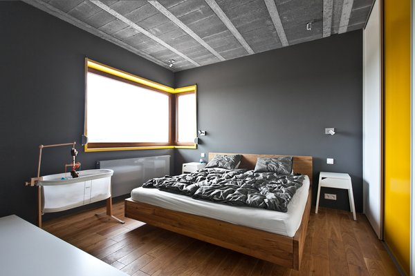 The bedrooms feel like sanctuaries, as they're much darker and enclosed than other spaces in the home.  Bedroom from A Modern Home Experiments with Exposed Concrete and Sliding Yellow Doors
