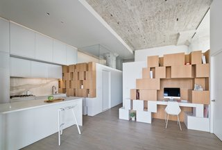 """The architect brought the solid walls of certain rooms down to 7' 8"""", filling the remaining 4' 2"""" with glass. This defining feature allows sunlight penetrate deep into the core of the space. The clients say the bright reds, oranges, and yellows of sunsets race across the ceiling and white walls."""