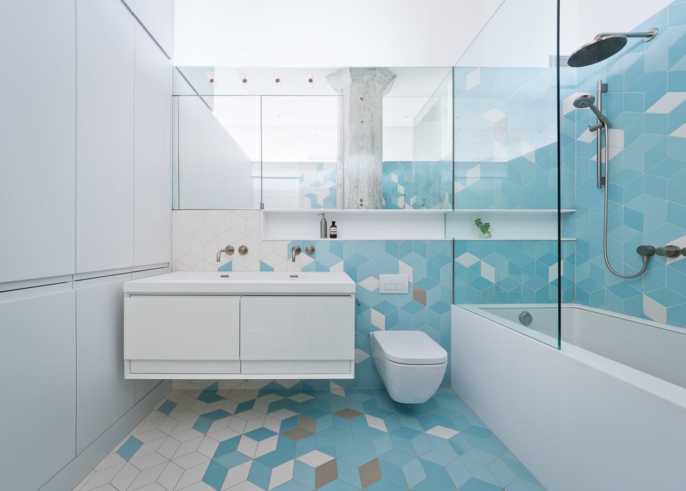 Bath, Wall Mount, Alcove, Ceramic Tile, Ceramic Tile, One Piece, and Open The bathroom, located just adjacent to the kitchen, features a pattern of gray and turquoise tiles that climbs from the floors up the walls. They serve as a burst of color among the predominately white walls elsewhere, transforming the bathroom into one of the apartment's most striking spaces.  Bath Open Alcove One Piece Photos from Brooklyn Loft Renovation Masters Storage with a Custom Cabinet Wall