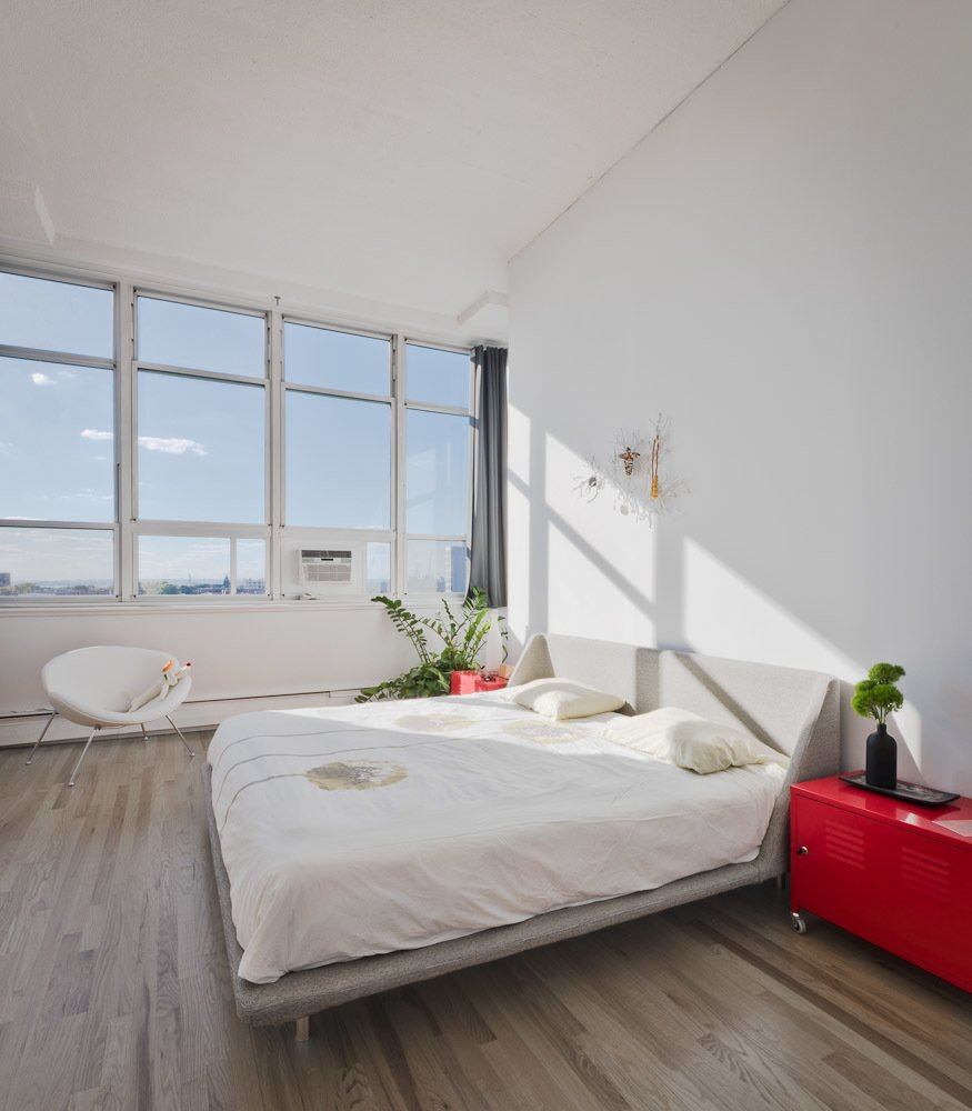 Bedroom, Bed, Storage, Chair, and Medium Hardwood Floor Last but not least, the western-facing master bedroom captures stunning sunsets from its wall-to-wall windows.  Blu Dot Spotted from Brooklyn Loft Renovation Masters Storage with a Custom Cabinet Wall
