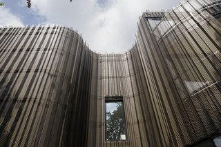 The plating of the facade imitates tree bark.