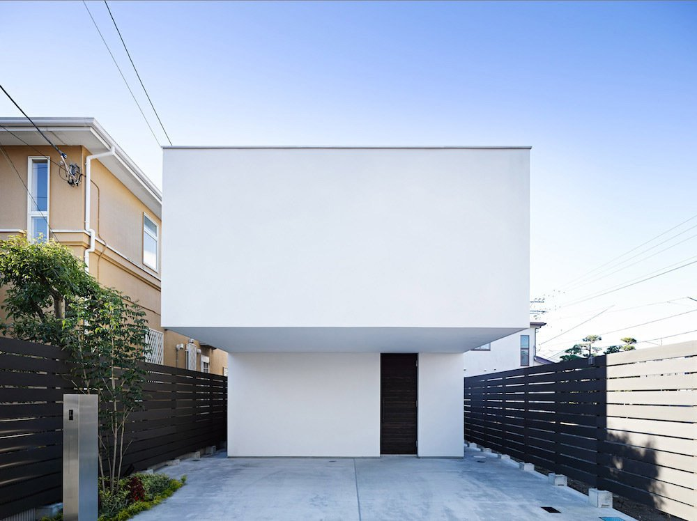 The façade designed by Apollo Architects and Associates features an overhanging upper level, which ensures that the entrance is pleasantly shaded and demarcates the property's two parking spaces. The home's wooden structure is clad in a bright white exposed concrete.  Unabashedly Strange Houses in Japan from This Modest Japanese Home is a Surfer's Paradise