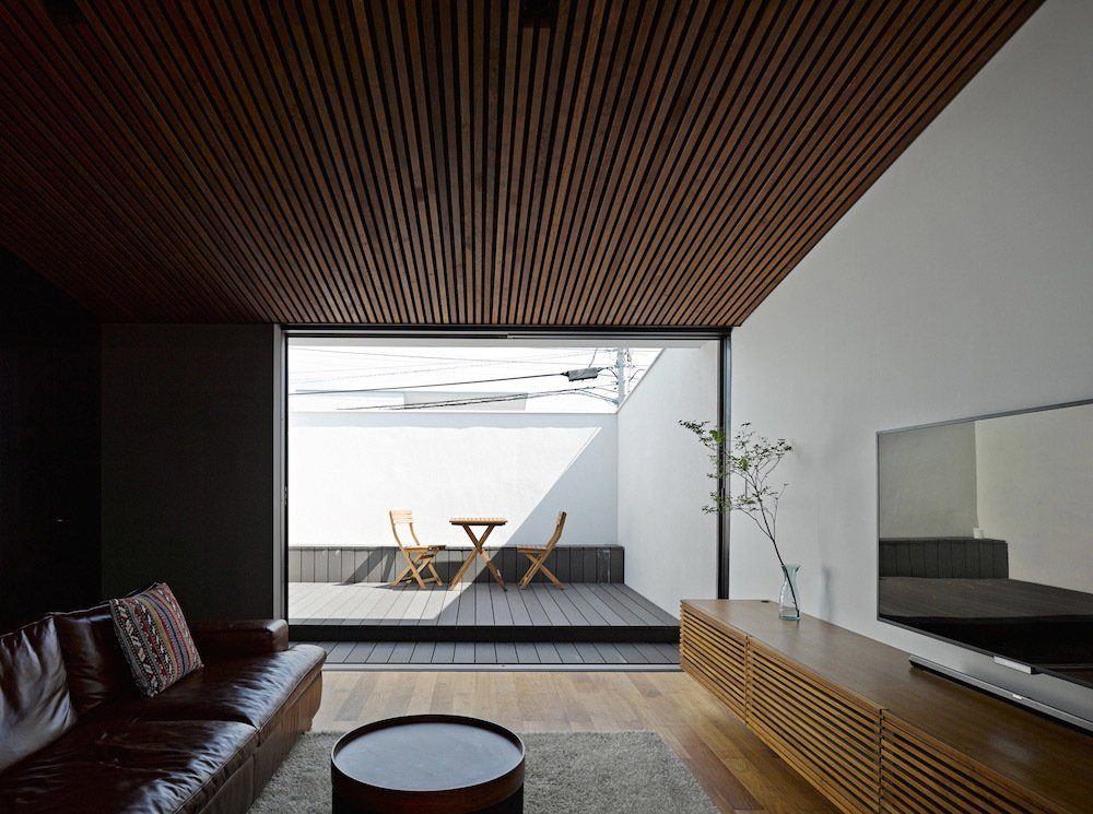 The living room also opens onto a private terrace, concealed within the entrance's cantilevered form. It serves as a secluded space to take in the sun. Thanks to the sizeable opening between the living room and terrace, it brings yet more light into the home. The terrace's table and chairs are from Ikea.  Private Rooftop Sanctuaries  by Zachary Edelson from This Modest Japanese Home is a Surfer's Paradise