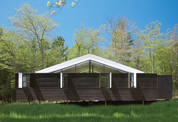 Nestled in a field of praire grass in the Wisconsin woods, the Weekn'der is a dynamic contrast of minimalist black and white. Charlie Lazor's design consists of two prefab modules bookending a central stick-built home. Photo by: George Heinrich