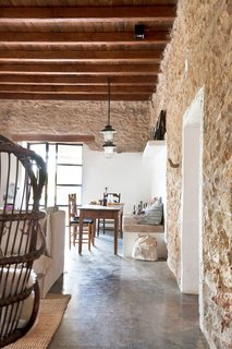 In Ibiza, a stunning modern-rustic getaway with unique features like rock walls, is the perfect summer retreat.