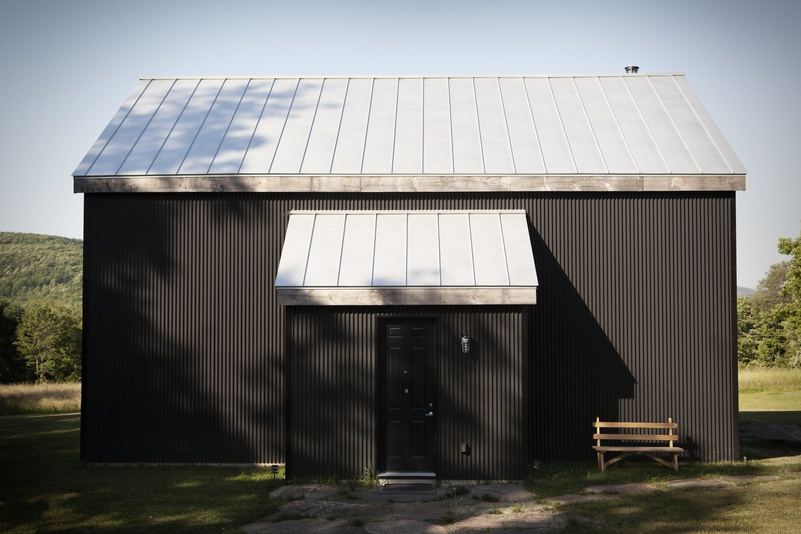 "Exterior, Cabin Building Type, Metal Roof Material, Gable RoofLine, and Metal Siding Material In Scandinavian regions, traditional cabins are painted black using a mixture of tar and linseed oil. Peck reproduced the look using corrugated metal—a lower-maintenance, more sustainable material. ""We love that it is black, because it really reminds us of home,"" Bronee says. The house has no windows on its front side, belying its light-flooded interior.  30+ All-Black Exterior Modern Homes by Zachary Edelson from A Slice of Scandinavian Design in the Catskills"