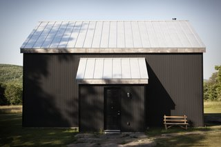 """In Scandinavian regions, traditional cabins are painted black using a mixture of tar and linseed oil. Peck reproduced the look using corrugated metal—a lower-maintenance, more sustainable material. """"We love that it is black, because it really reminds us of home,"""" Bronee says. The house has no windows on its front side, belying its light-flooded interior."""
