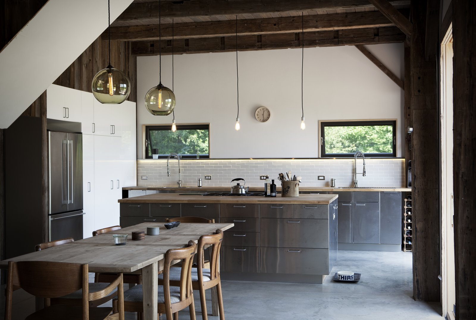 Kitchen, Metal Cabinet, Wood Counter, and Pendant Lighting Originally from Norway, photographer Torkil Stavdal and nutritionist Jeanette Bronée brought a slice of their native Scandinavia to the Catskills when they collaborated with architect Kimberly Peck to design their dream home. In the dining area, Danish modern chairs purchased at Circa Modern are tucked into a wood table from Restoration Hardware. The kitchen cabinets, counters and sink are from IKEA with faucets from Danze.  Photo 15 of 15 in Heavy Metal: 15 Kitchens That Rock Metal Cabinets from A Slice of Scandinavian Design in the Catskills