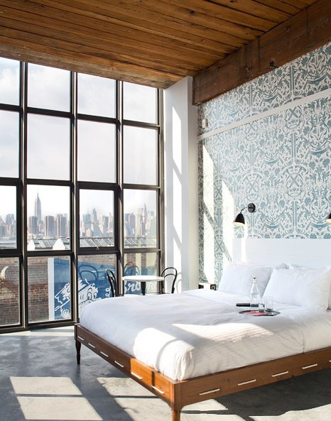 A bedroom with a view of Manhattan in the Wythe Hotel.  Bedroom from Photographers We Love: Mark Mahaney