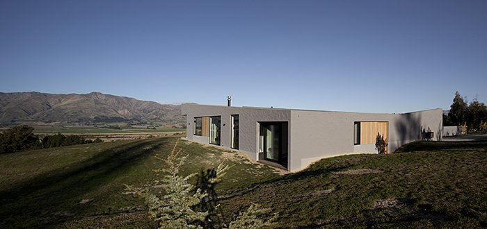 The living, dining, and sleeping spaces occupy the northern and eastern edges of the house, following the direction of the southern hemisphere sun. Niches and overhangs in the building protect it from the hot, dry summers and harsh winters.  Lake Hawea Courtyard House by Sam Eichblatt