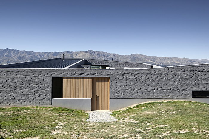 The protective wall is broken with small apertures, like this wood-panelled door that slides back to allow entry.  Lake Hawea Courtyard House by Sam Eichblatt