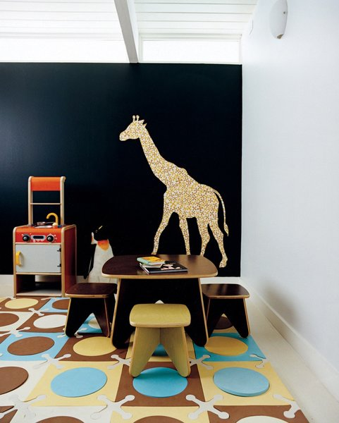 A patterned giraffe wall decal sticks itself onto the deeply saturated blue hued wall in this modern playroom in Portland, Oregon. Photo by: John Clark. (Pin).