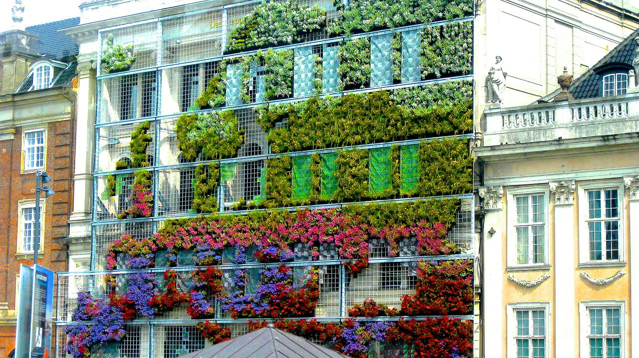 Exterior and Green Siding Material To raise awareness about biodiversity in cities and the benefits it delivers, the EEA façade, overlooking one of the most prominent squares of Copenhagen, Denmark, gets shielded with a vertical garden (shaped like a map of the European continent!) which uses a mesh pattern, similar to a cross-stich pattern, that fills in dirt and various flowers. Via WalkOnWaterOrDrown.  Photo 8 of 10 in Living Green Walls 101: Their Benefits and How They're Made from Day of the Living Wall