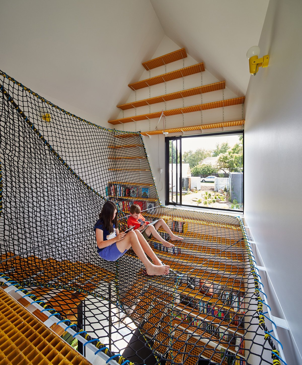 Kids Room and Playroom Room Type Spinning off the living room on the north side of the main house, the children's study sits separately from the other pavilions. On its upper level, Oxley netting forms a web on which the kids and their friends can sit and read with views of the leafy street and garden.  Loft from This Transformed Melbourne House Resembles a Quirky Village
