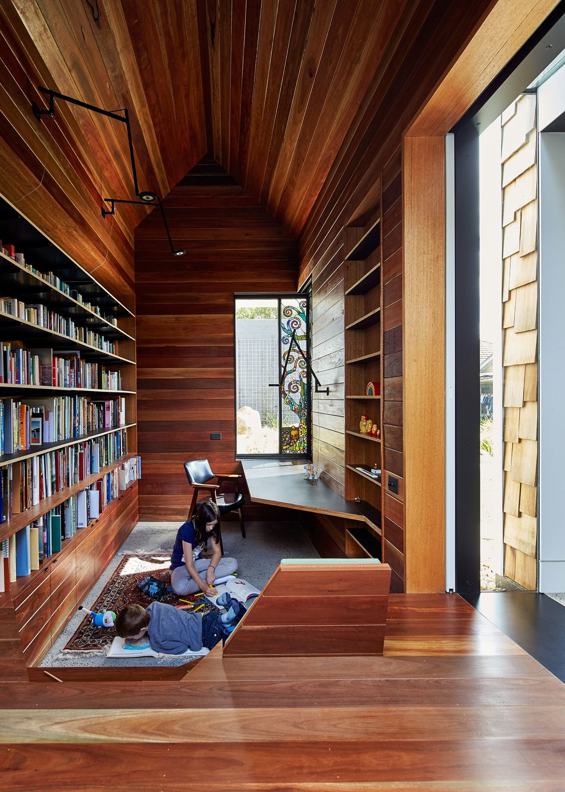 "Office, Library Room Type, Medium Hardwood Floor, and Bookcase The library is lined in reclaimed spotted gum that Maynard says ""brings with it wisdom from its previous life."" A stained glass window by Leigh Schellekens makes the contemplative room feel like a domestic chapel.  Photo 10 of 12 in This Transformed Melbourne House Resembles a Quirky Village"