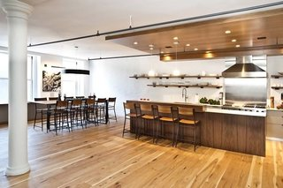 In the open-plan space, a dropped ceiling in walnut helps define the kitchen area. Throughout the apartment, wide planks of hickory make up the flooring.