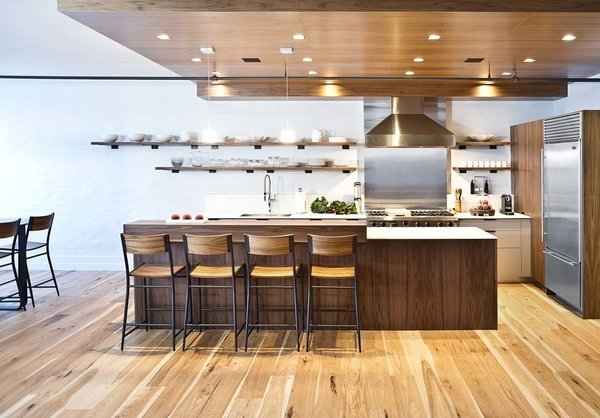 Recessed ceiling lights, speakers, and the range hood ductwork are all concealed by the dropped ceiling. The stools are West Elm.