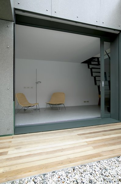 A wall-sized sliding window opens the downstairs living area up to a intimate atrium-style outdoor area. A narrow deck, which is screened from the surrounding houses, brings an astonishing amount of indirect sunlight into the ground floor.  190+ Best Modern Staircase Ideas from 100-Year-Old Service Shed in Slovenia Becomes a Miniature Home