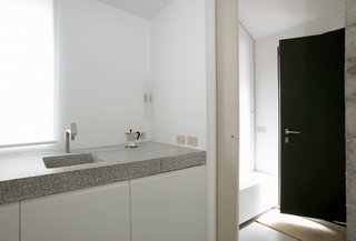 The concept of raw materials was carried through on the interior, using plywood and a slab of terrazzo for the kitchen, which features Bulthaup fittings.