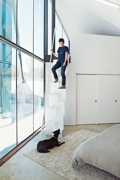 Like the pavilion holding the public spaces, the structure containing the bedrooms is clad in glass on the interior sides facing the courtyard, allowing a constant connection to the outside. Rodriguez (with dog Lupe) designed the steel stairs leading from the mezzanine-level home office to the master bedroom below. The stairs were fabricated by Austin-based Steel House MFG.