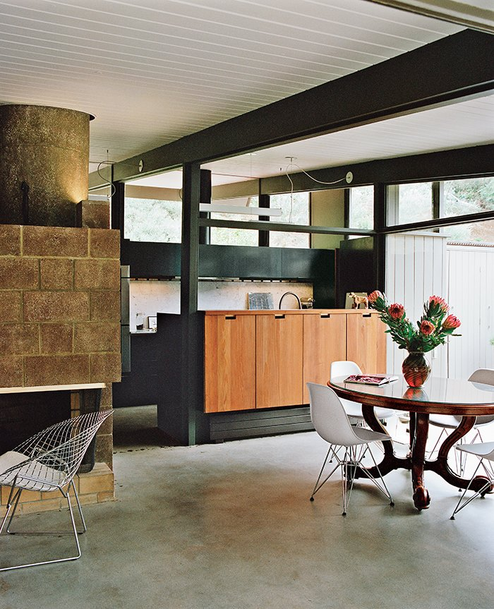 Dining Room, Table, Wood Burning Fireplace, Chair, Concrete Floor, and Standard Layout Fireplace The duo added custom redwood cabinetry on the dining area side. The pendants are from Birchwood Lighting.  Raconteur Renovations: Homes with Some Serious History by Matthew Keeshin from L.A. Renovation Respects Midcentury Bones (While Adding Some Flair)