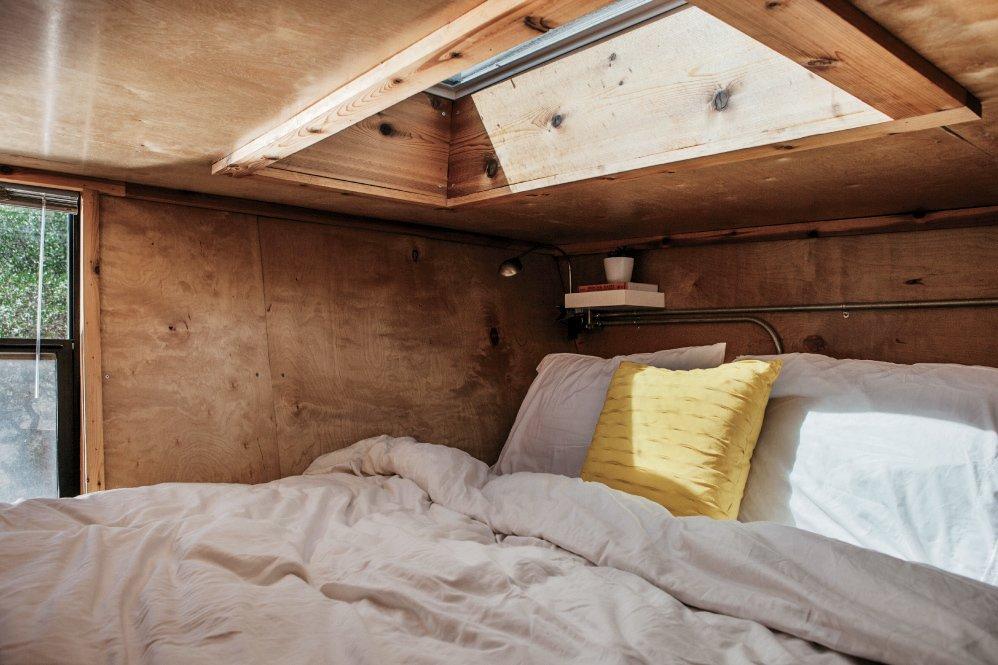 Woody camper trailer bedroom with skylight and corner shelf