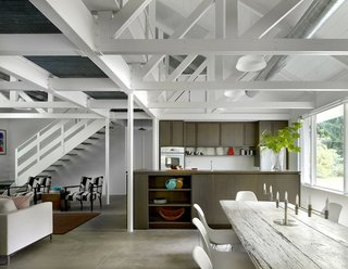 Completed in 2013, the roughly 1,500-square-foot cabin provides an open living area framed by white trusses and concrete floors. The dining table was acquired by the owner from a local inn, and is surrounded by the Eames molded plastic Eiffel side chairs from Design Within Reach. The kitchen features a Grohe faucet, a wood bowl from a shop in Harbert, and an Ikea vase.