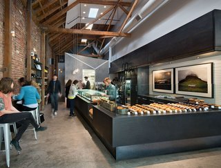 Housed in a brick and timber Mission building that saw past lives as both a hotel and auto repair shop, Craftsman and Wolves was created by founder and chef William Werner using simple materials and a relatively modest budget. Werner collaborated closely with Zack | de Vito Architecture + Construction to bring to light his vision for a modern pâtisserie that was masculine and industrial. A cool-toned interior palette is favored, with black quartz counters at the bar and steel-trowel stucco cement walls along the kitchen's perimeter. Modest IKEA cabinetry is seamlessly integrated with custom Italian glass refrigerated pastry cases. 746 Valencia Street