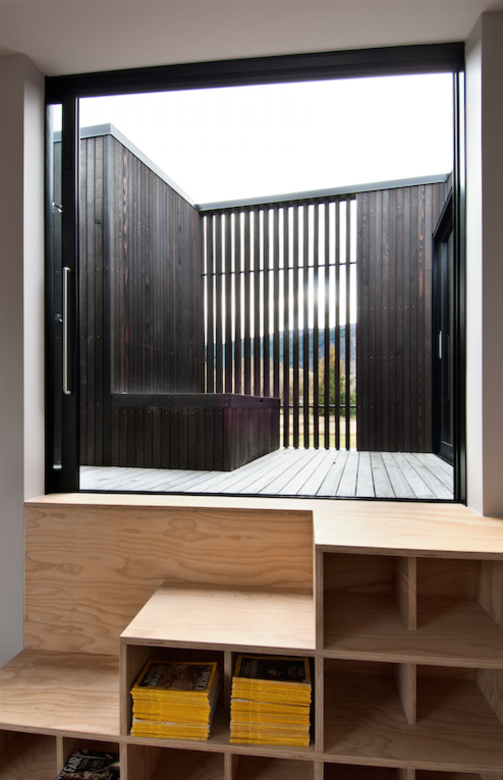 """A clever combination bookshelf and staircase in the children's bedroom leads to the interior """"star-gazing"""" deck, which is invisible from the ground, and contains an open-air bathtub and a sauna. It is also accessible from an adjacent guest bedroom.  """"The house is not huge but uses comparative spaces to create different experiences — it's also about enjoying life and not being overly serious, hence these perceived 'follies' such as the deck. Those non-traditional elements have given the house a different flavor,"""" says Cooke.  190+ Best Modern Staircase Ideas from This Kid-Friendly Home is Full of Surprises"""
