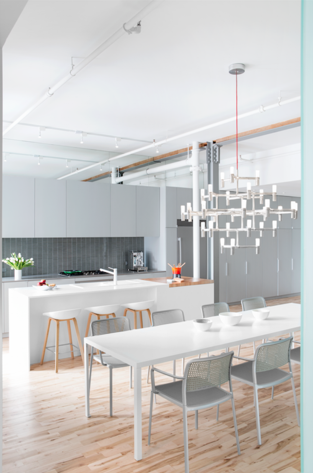 The space was reoriented in order to accommodate a third bedroom for the residents' second child. The adjustment required reducing the size of one of the existing bedrooms and relocating the kitchen, which now is an open-plan space next to the living room. A Major Crown chandelier by Nemo hangs above a Zeus-Noto table and Kartell chairs.  Luminous Modern Apartment in an Industrial Montreal Building by Allie Weiss