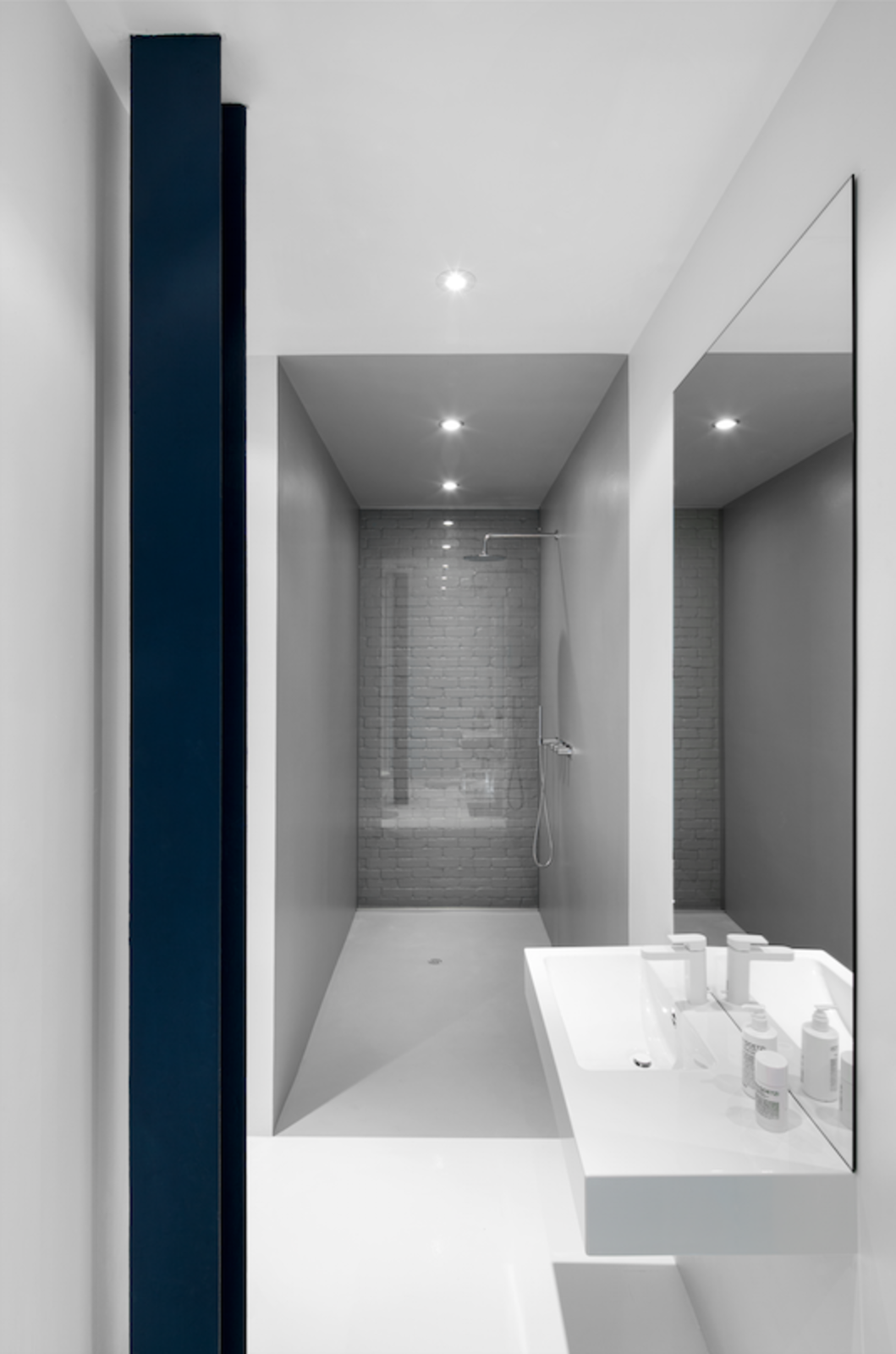 The bathroom contains white epoxy flooring, while the Cabano Bath shower is lined in gray epoxy.  Luminous Modern Apartment in an Industrial Montreal Building by Allie Weiss
