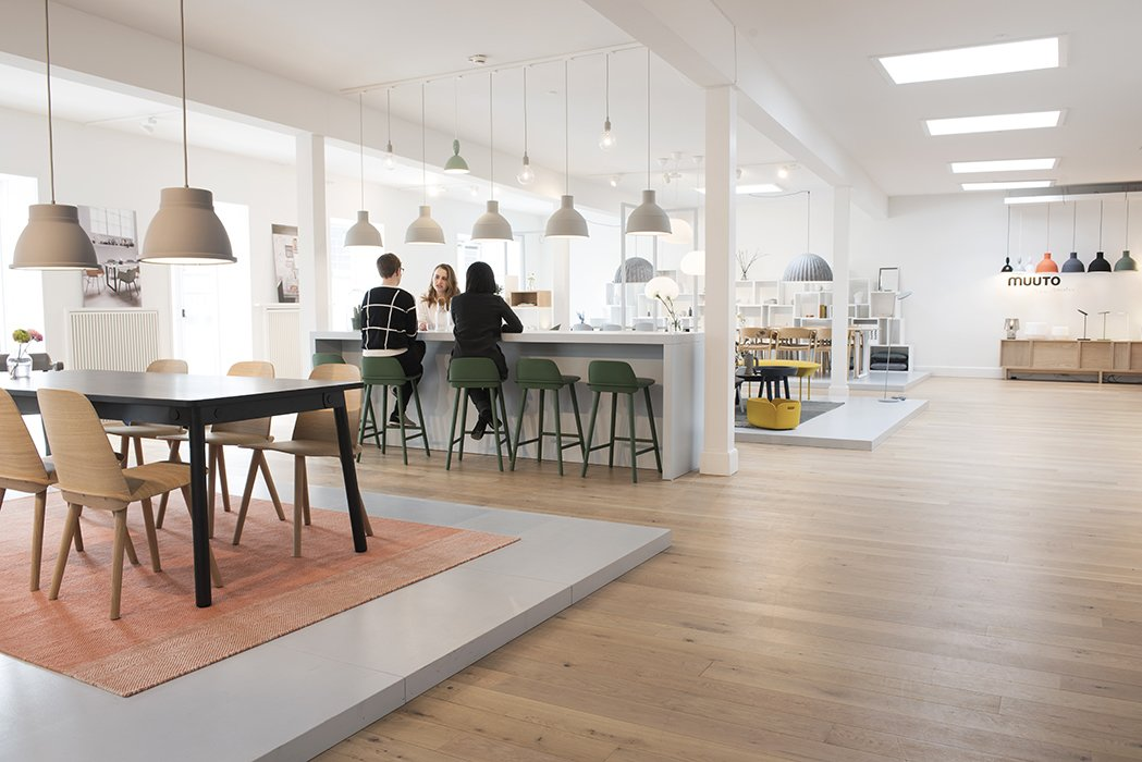 """Muuto's full collection is on display in their spacious showroom, where individual environments are dedicated to different rooms of the home. The showroom also functions as a meeting place. """"Because the number of employees at Muuto is growing, we sometimes have a lack of meeting rooms,"""" explains project manager Nina Bruun. Impromptu gatherings give visitors an opportunity to see Muuto's collection come alive through organic interactions.  Photo 2 of 7 in Muuto's Sophisticated Copenhagen Office is All About Transparency"""