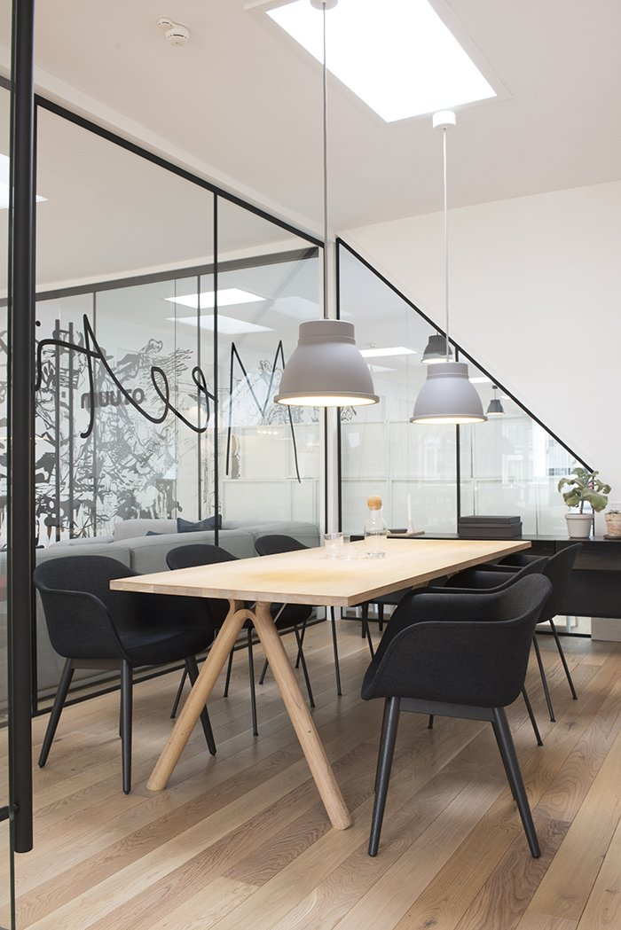 The subdued color scheme is also evident in the conference room. Floor-to-glass glass walls underscore the company's commitment to transparency, even in the most private spaces. The room is illuminated by grey Studio pendant lamps by Thomas Bernstrand.  Photo 6 of 7 in Muuto's Sophisticated Copenhagen Office is All About Transparency