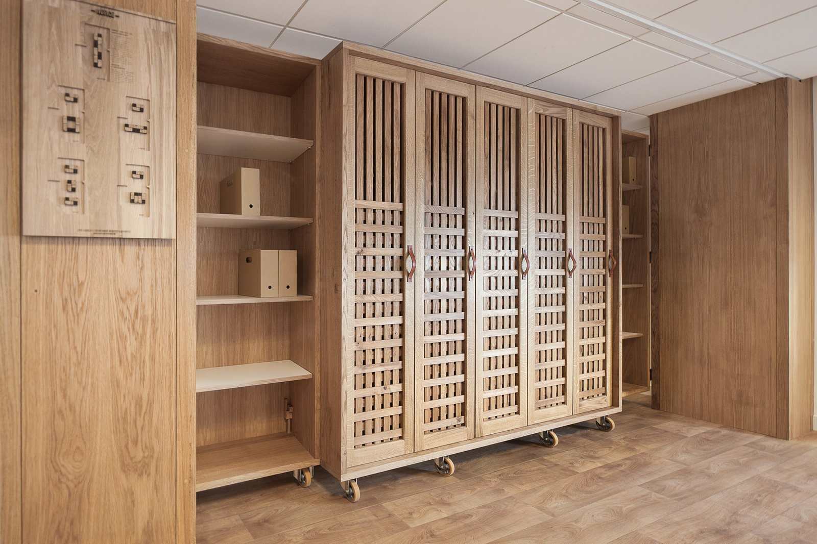 A wooden wardrobe provides storage, while a carved and burnt-wood board provides visual instructions explaining the room's possible configurations  Photo 5 of 6 in A Modular Meeting Room Features a Table with 6 Possible Layouts