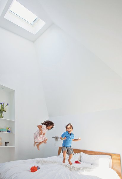 """Zoe and Jake horse around in their parents' new master bedroom. Issa says he vaulted the ceiling to fit under the addition's angular roofline for """"spatial impact."""" Paint is Extra White by Sherwin-Williams."""