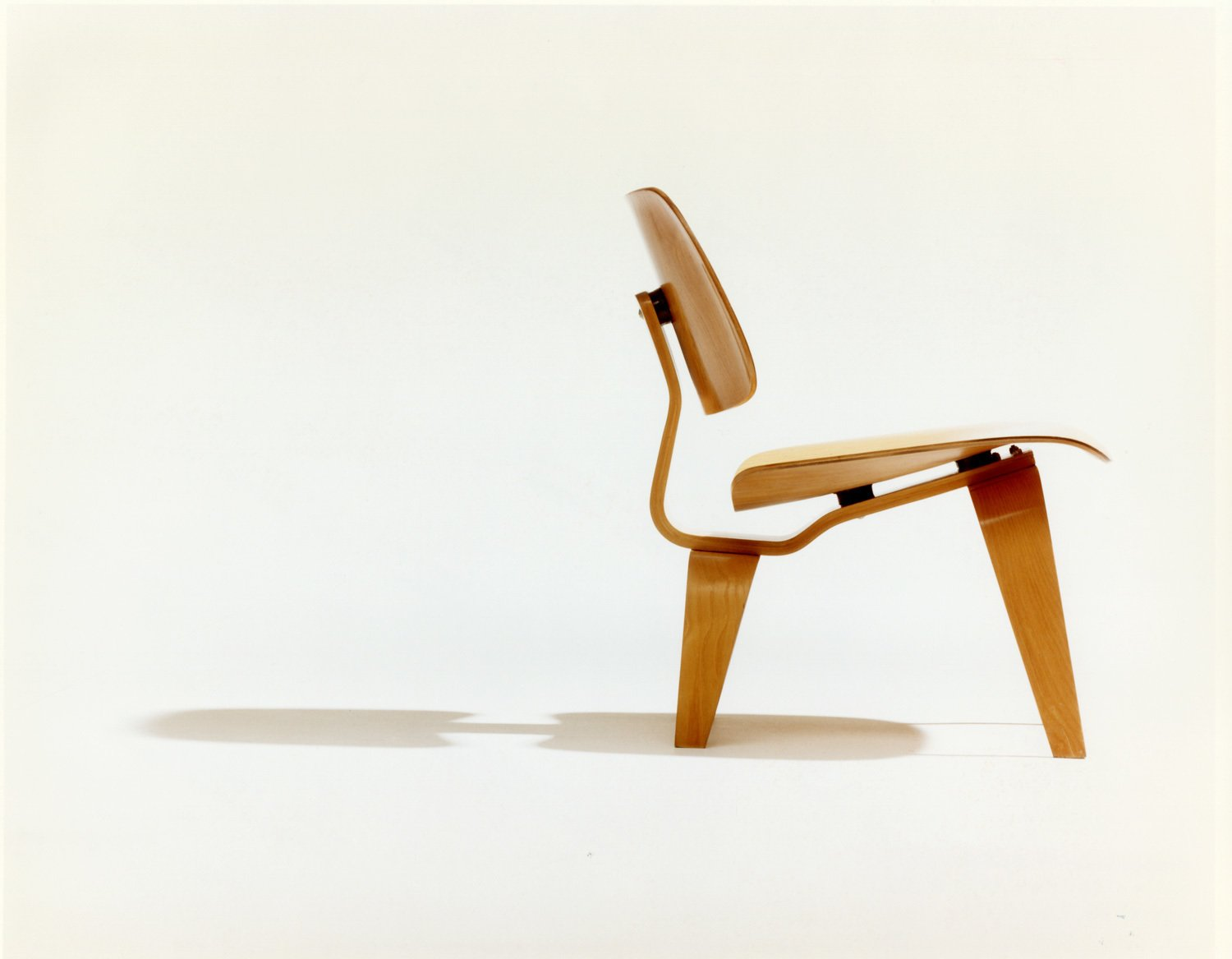 A photograph by Phil Schaafsma highlights the ergonomic design of the chair.  Photo 4 of 8 in A Leg Splint Inspired Charles and Ray Eames' Famous Molded Plywood Lounge Chair